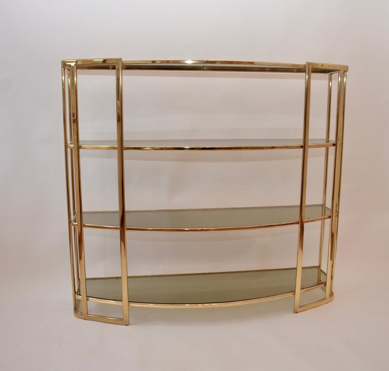 A midcentury Romeo Rega étagère, Renato Zevi 1970s piece. Lovely brass frame with tinted glass shelves. There is a genuine label to the base of the item.