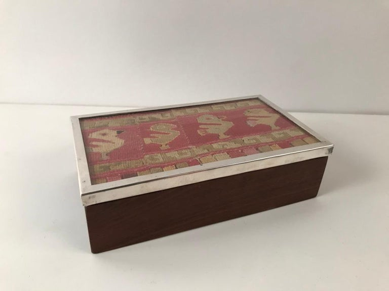 Wonderful midcentury Peruvian rosewood box with a sterling silver framed lid. The lid made up of a charming piece of Chancay culture textile depicting a row of four birds or ducks in amusing aspect. I've always found these early textiles to be