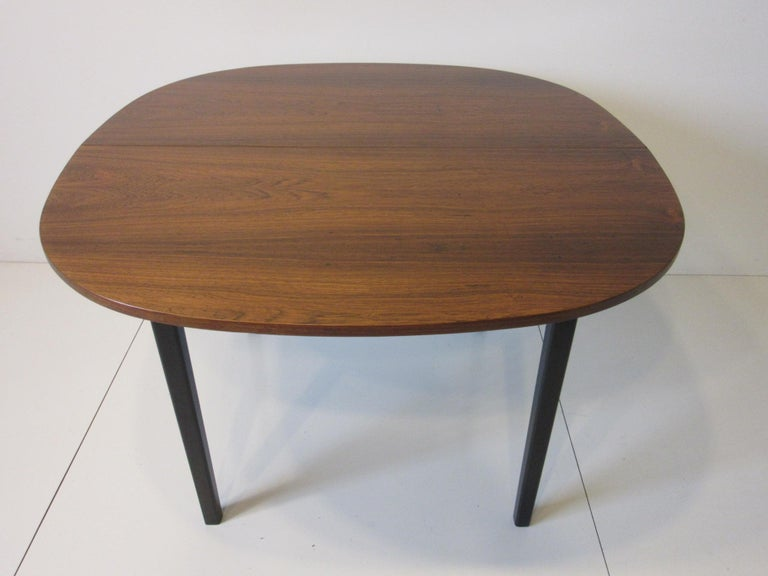 A well grained book matched Brazilian rosewood dining table with two 15