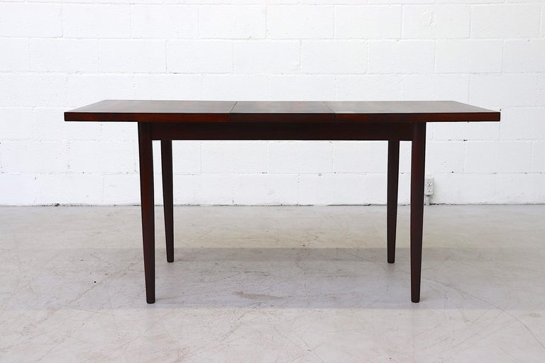 Beautiful rosewood dining table with hidden leaf and lightly refinished with round wood legs. In original condition with wear consistent with age. Table extends to 62.5