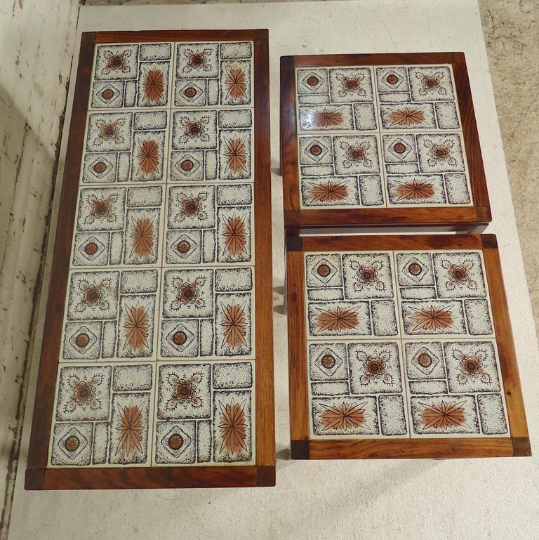 Set of three tile top tables with rosewood frames. Two tables nest inside the larger table.  (Please confirm item location - NY or NJ - with dealer).