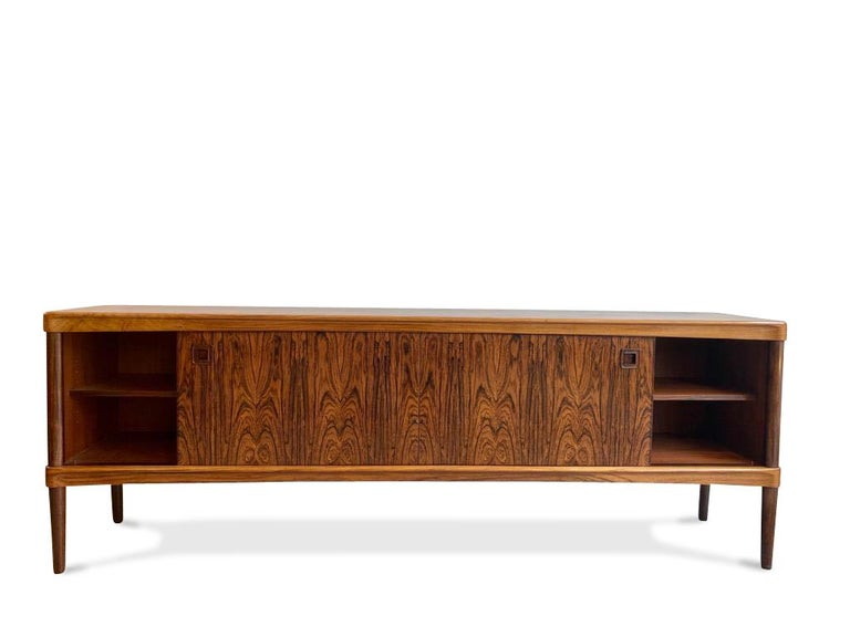 This high quality Danish rosewood sideboard was designed by H. W. Klein for Bramin, 1960s.  Features two sliding doors either side concealing shelves and 5 central drawers set on thin legs.   Really beautiful color and wood grain pattern.