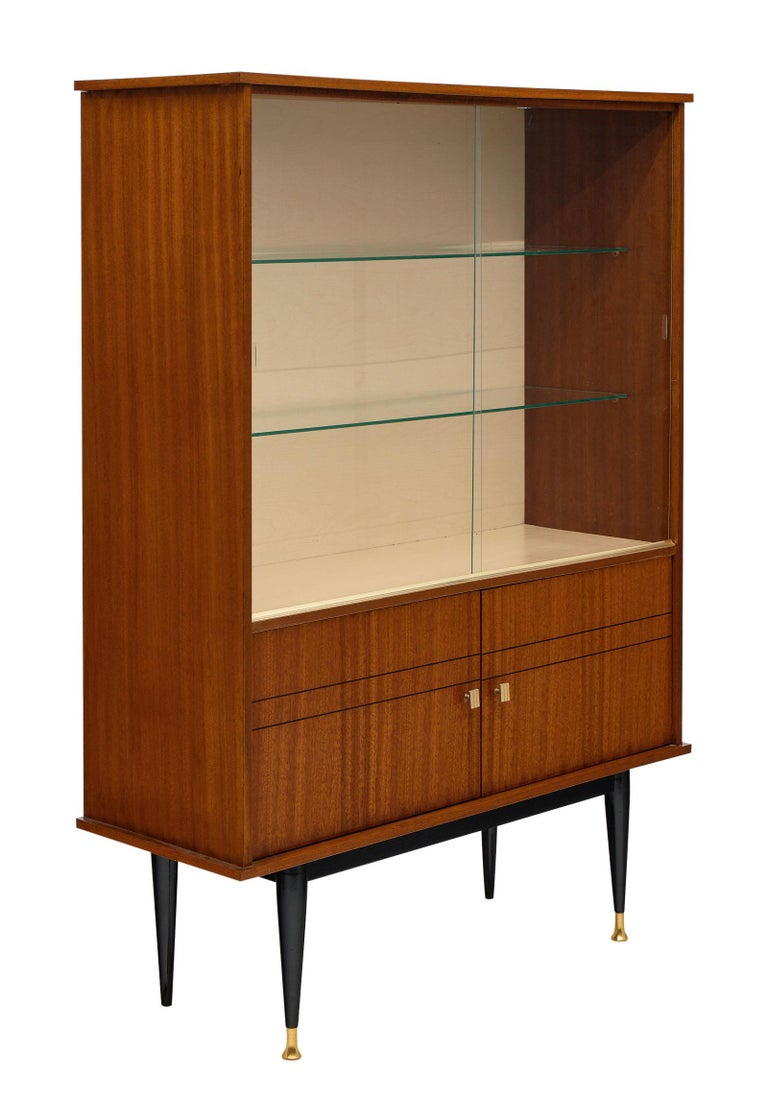 Mid-Century rosewood French silver cabinet with glass shelving behind two original glass sliding doors. We love the detail of this elegant piece and the tapered; ebonized legs capped with brass. the bottom doors open out for additional storage.