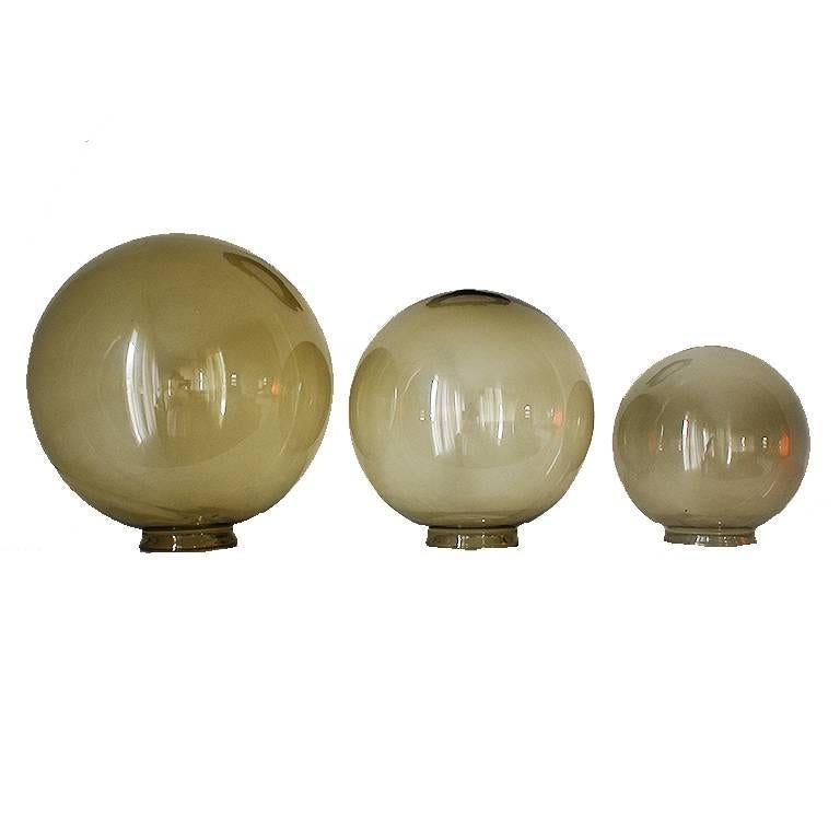 Three glass orbs sold as a set. Makes a gorgeous statement piece for a coffee table, dining table or credenza. Each very in size and feature a beautiful green/brown hue. 