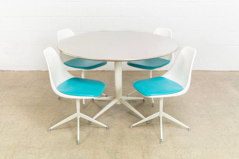 • Vintage Mid-Century Modern Burke tulip table and chairs in the style of Eero Saarinen, circa 1960. • Iconic tulip style design with clean lines and elegant curves. • Rare Burke star chair and table base design with silver metal floor glider