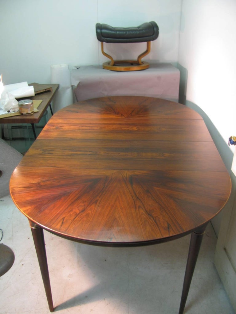 Round with inlay crouch rosewood design. Turned legs which are capped with solid brass rings. Table has two leaves which are 15.75 inches each. Table with both leaves in is 78.5 total.