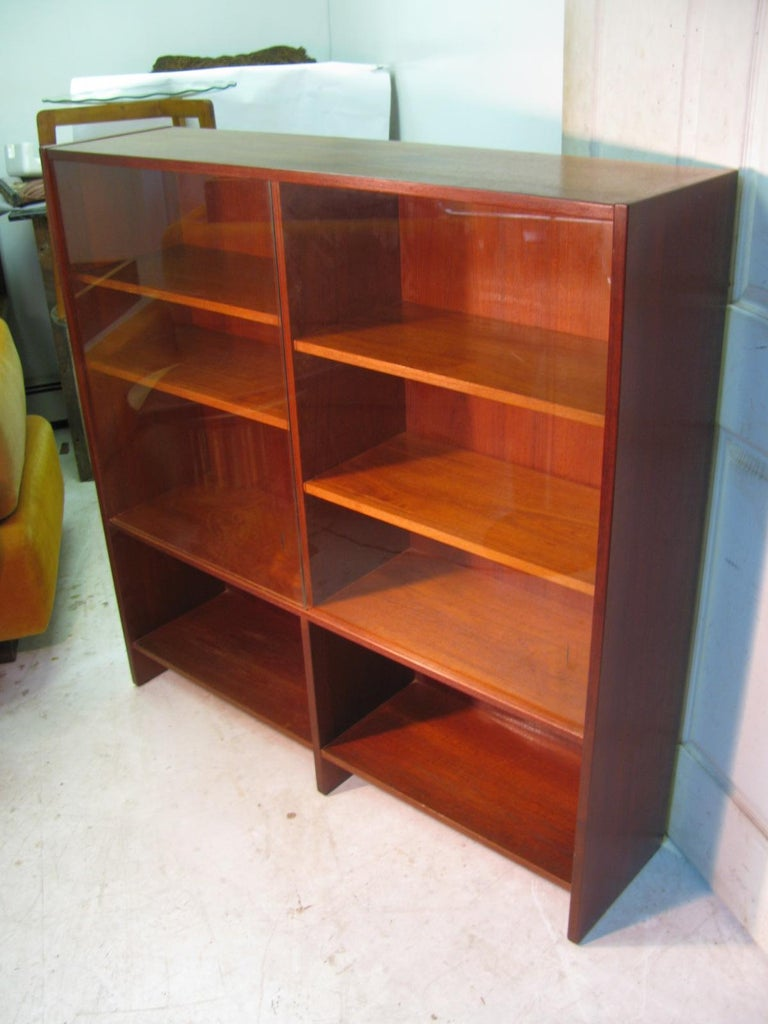 Midcentury teak bookcase with glass sliding doors. Four adjustable shelves with two fixed shelves at the bottom. Very good condition, no chips to glass.
