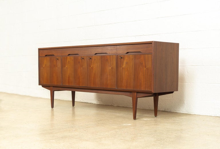 This vintage midcentury Scandinavian Modern credenza sideboard was designed by Alf Aarseth for Gustav Bahus and made in Norway circa 1960. Exceptionally crafted from walnut with beautiful natural grain, this extra wide cabinet features three