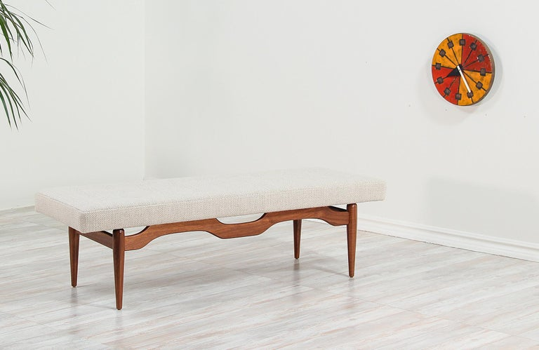 Mid-Century Modern bench designed and manufactured in the United States, circa 1950s. A comfortable modern bench featuring a sculptural solid walnut wood base and new tweed upholstery with an elegant tufted detail making an excellent option for