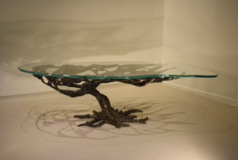A unique cast bronze coffee table in the shape of a tree with an exceptionally beautiful dark green patina. This patina is similar to that used by well-known artists such as Alberto Giacometti and other contemporaries The thick tabletop has an
