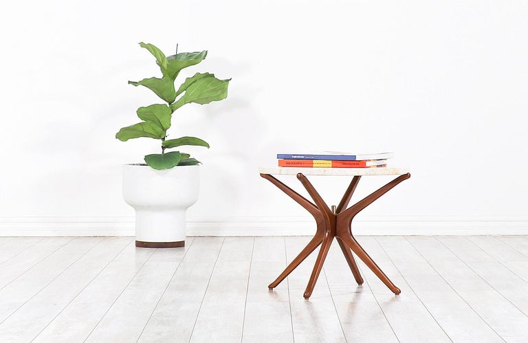 Stylish Mid-Century Modern sculpted Jax side table designed and manufactured in Italy circa 1950s. This sleek design features an atomic Jax-shaped walnut wood base with a brass pin in the center of the structure, adding an elegant touch to the