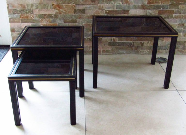 French vintage set of three nesting tables by Pierre Vandel in black lacquered aluminium with brass accents and black glass tops. Signed on top.