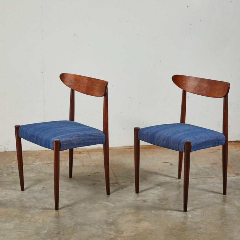 Pair of Mid century dining chairs with tapered legs upholstered in a textured blue fabric.