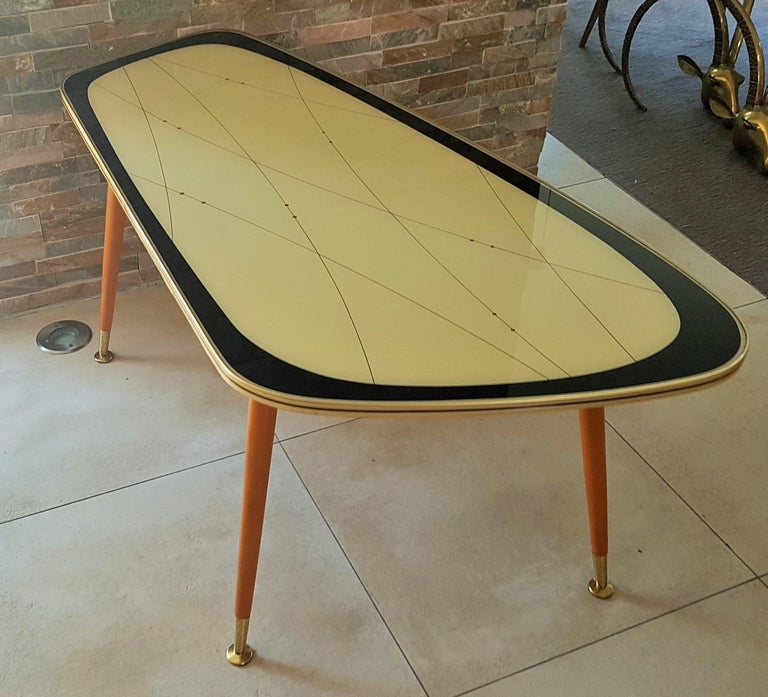 Midcentury side coffee table, Germany 1950s. Black gold Ivory laquer under glass. UFO legs with brass feet. Very good vintage condition.