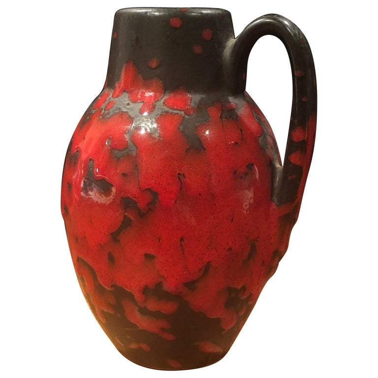 A very cool midcentury single handle lava glazed vase made in West Germany, circa 1970s. The vase has a dark brown base with a bright red lava glaze and measures 4.5