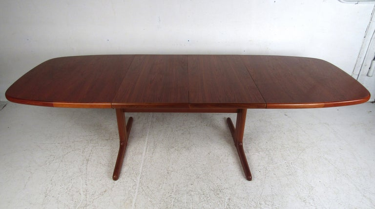 This stunning vintage Danish modern dining table boasts an unusual sled leg base with a stretcher that runs horizontally for added support. Two leaves enable this dining table to extend from 65 inches wide all the way to 104.5 inches wide ensuring