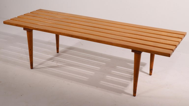 Iconic slat bench coffee table, made in Yugoslavia. This examples solid maple, unusual to see this form in the blonde finish, as most are in dark wood. Classic architectural Mid Century design, simple, chic and sophisticated. The table is in good,