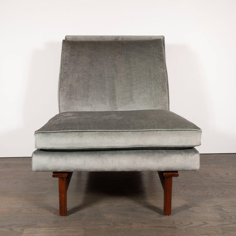 This refined Mid-Century Modern slipper chair was realized by the esteemed Danish designer of the period Jens Risom, circa 1950. With its elegantly austere form, the beauty of this piece is in the details: its sculptural side slats, subtly tapered