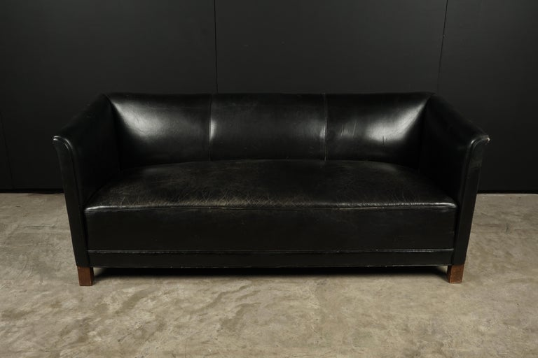 Vintage leather sofa manufactured by Fritz Hansen, Denmark, circa 1960. Original black leather upholstery with legs of beech.