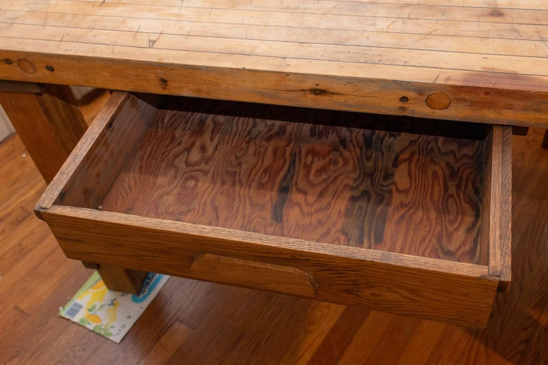 This large, vintage solid wood worktable features a butcher-block style top with two drawers. This piece would make a fantastic kitchen worktable or island, which can double as an eating area. Each leg is removable, making it much easier to