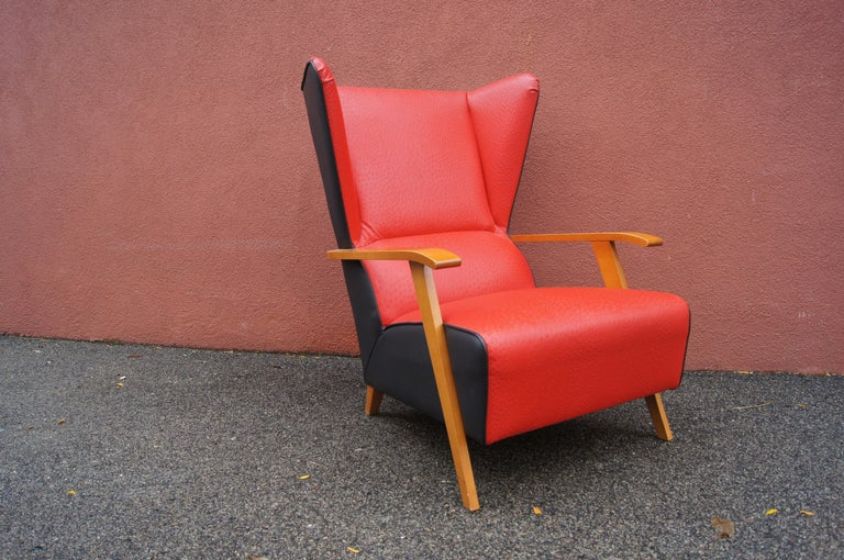 This midcentury Spanish lounge chair features an angular maple frame with a dramatic high back, made more striking by the contrast of ostrich-print red leather in front and black leather in back.