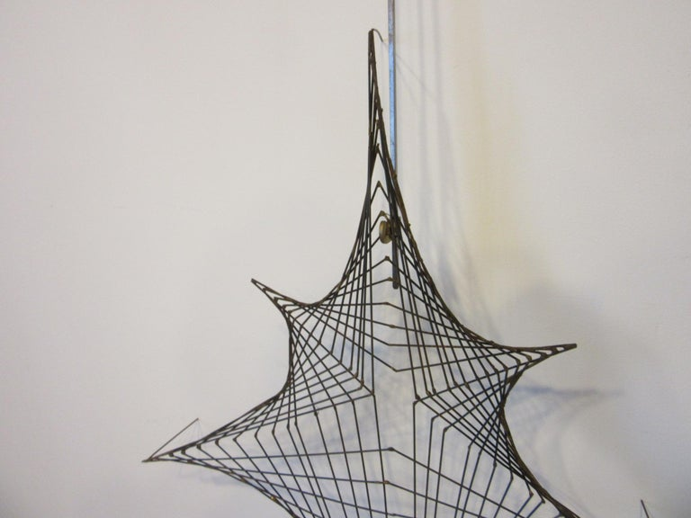 A very well crafted fine wire welded wall sculpture in the manner of a spider web while hanging it sits 3