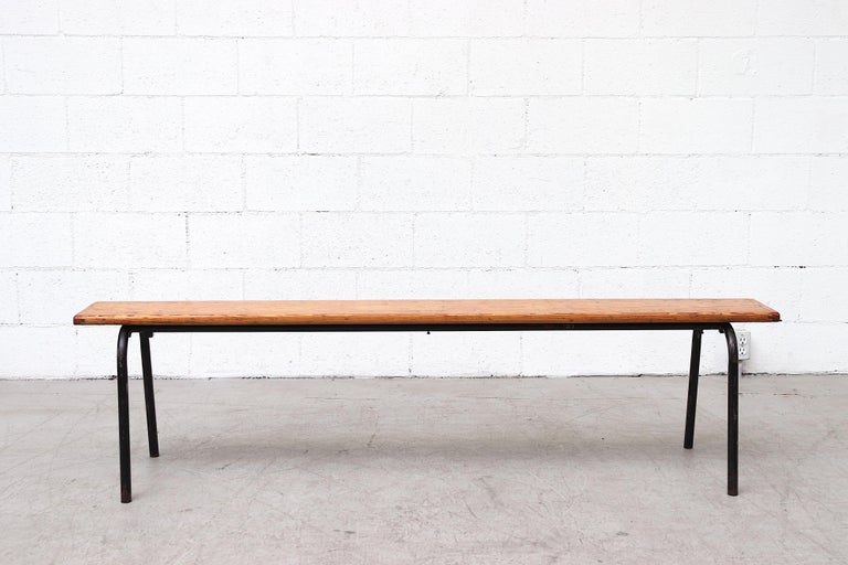 Vintage stacking wood gymnasium benches with tubular brown enameled metal legs and visible wear. In original condition with scratches and enamel loss consistent with age and use, visible patina to the gloss wood seating. Priced individually.