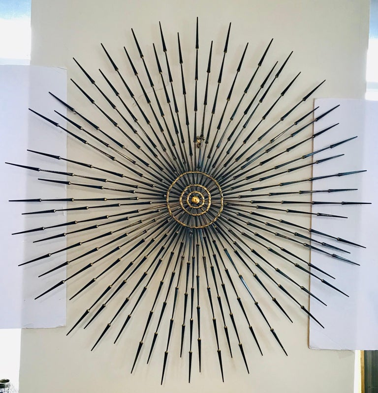 A large Brutalist sunburst with starburst overlay nail art wall sculpture by Ron Schmidt. It is made up of copper, metal, brass and iron. This sculpture features a multi-planar design with brass welded iron nail rays radiating sunburst-style from a