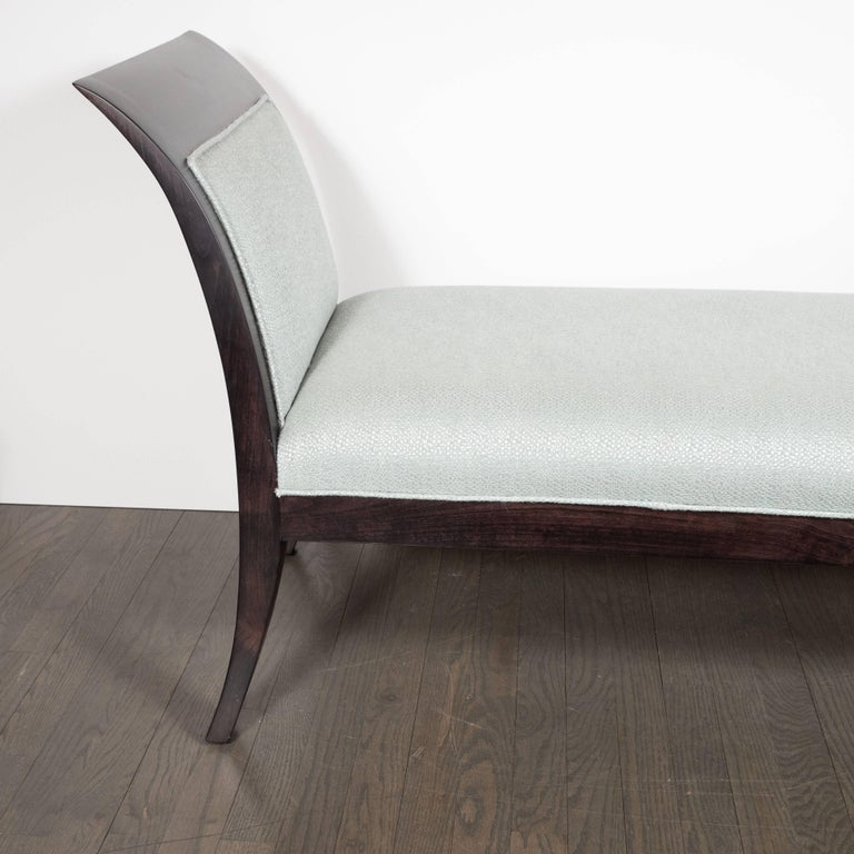 This sophisticated Mid-Century Modern bench features two streamlined sides in the United States, circa 1950. The bowed form of each side is reiterated in palindromic symmetry in the saber style legs upon which it rests, all realized in ebonized