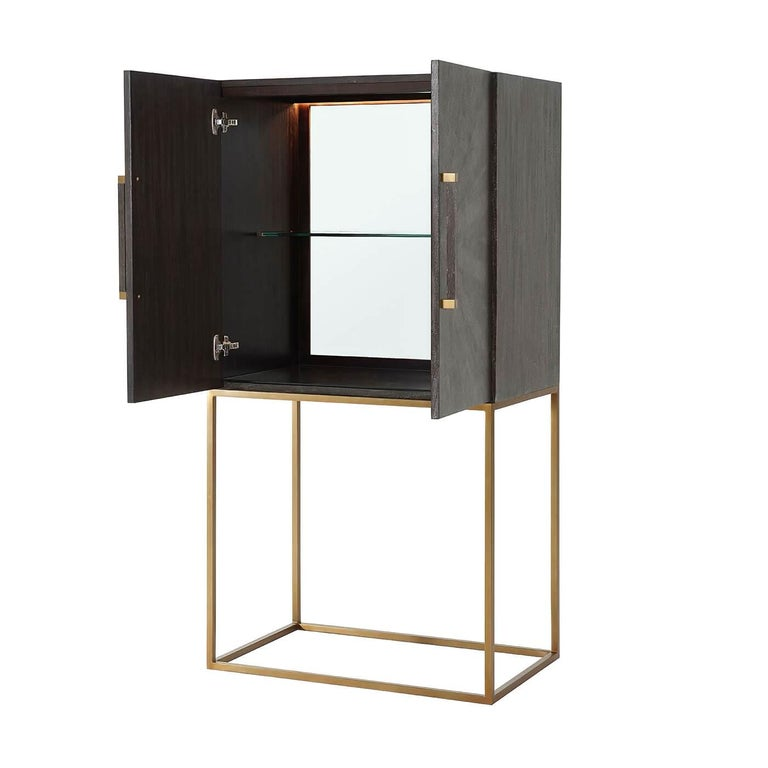 Midcentury style leather-wrapped bar cabinet with a primavera veneered case in our tempest finish starburst komoda embossed leather doors, with square baton handles with polished nickel finish clasps, polished nickel finish open cube base with a
