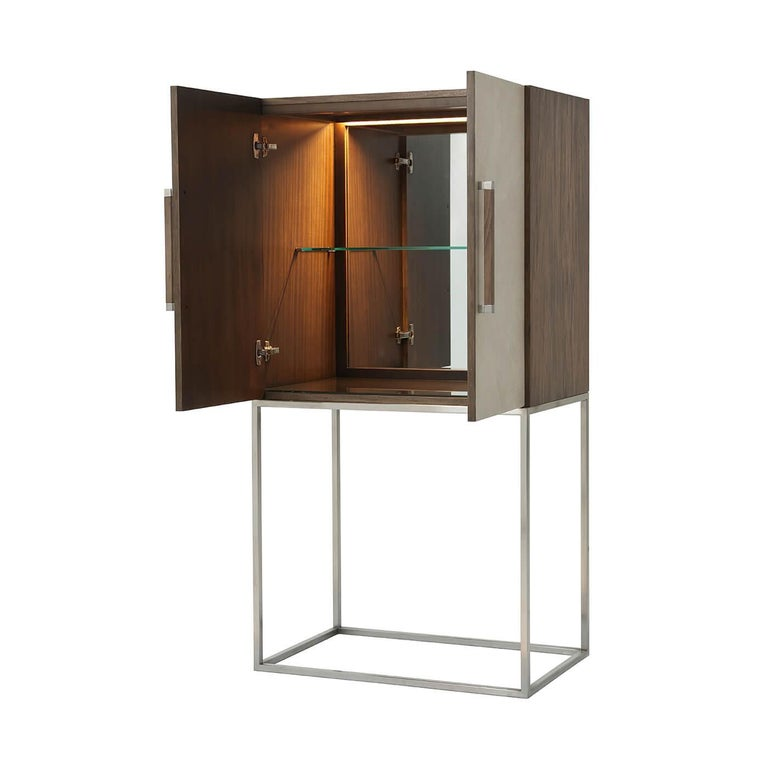 Midcentury style leather-wrapped bar cabinet with a primavera veneered case in our mangrove finish with overcast finish starburst komoda embossed leather doors, with square baton handles with polished nickel finish clasps, polished nickel finish