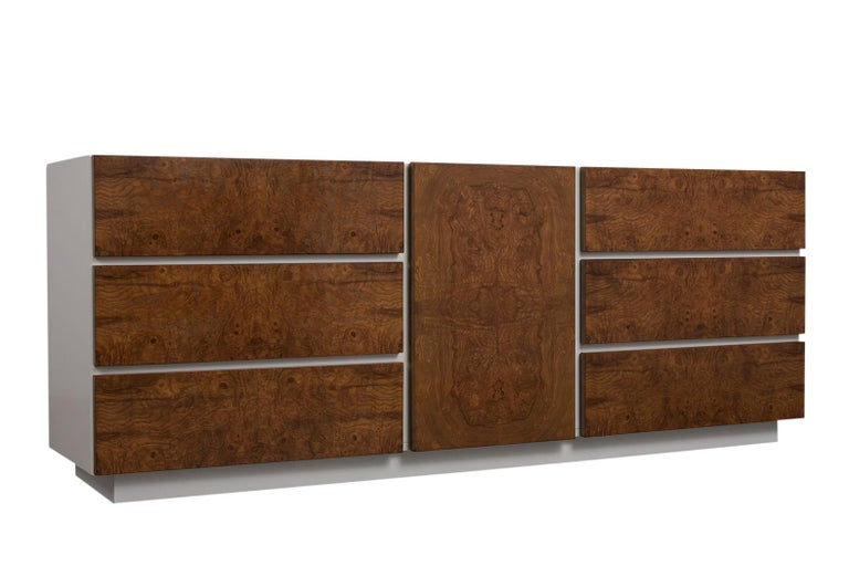 This 1970s Mid-Century Modern burled elm dresser has been professionally refinished in walnut and white color combination with lacquered finish. There are three large drawers on each side and a center door with three small pullout / pull-out drawers