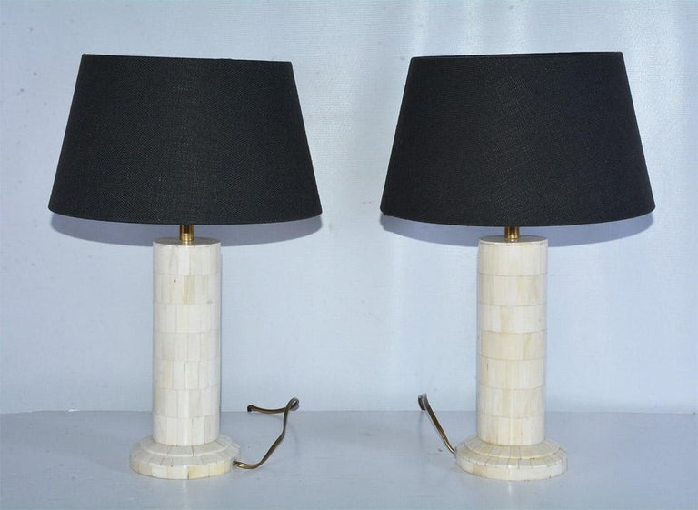 Pair of slender cylinder shape lamp base decorated with polished inlaid square bone mosaic paired with black Belgium linen lamp shade. Euro style lamp socket. Measures: Height of lamp with shade 18.50