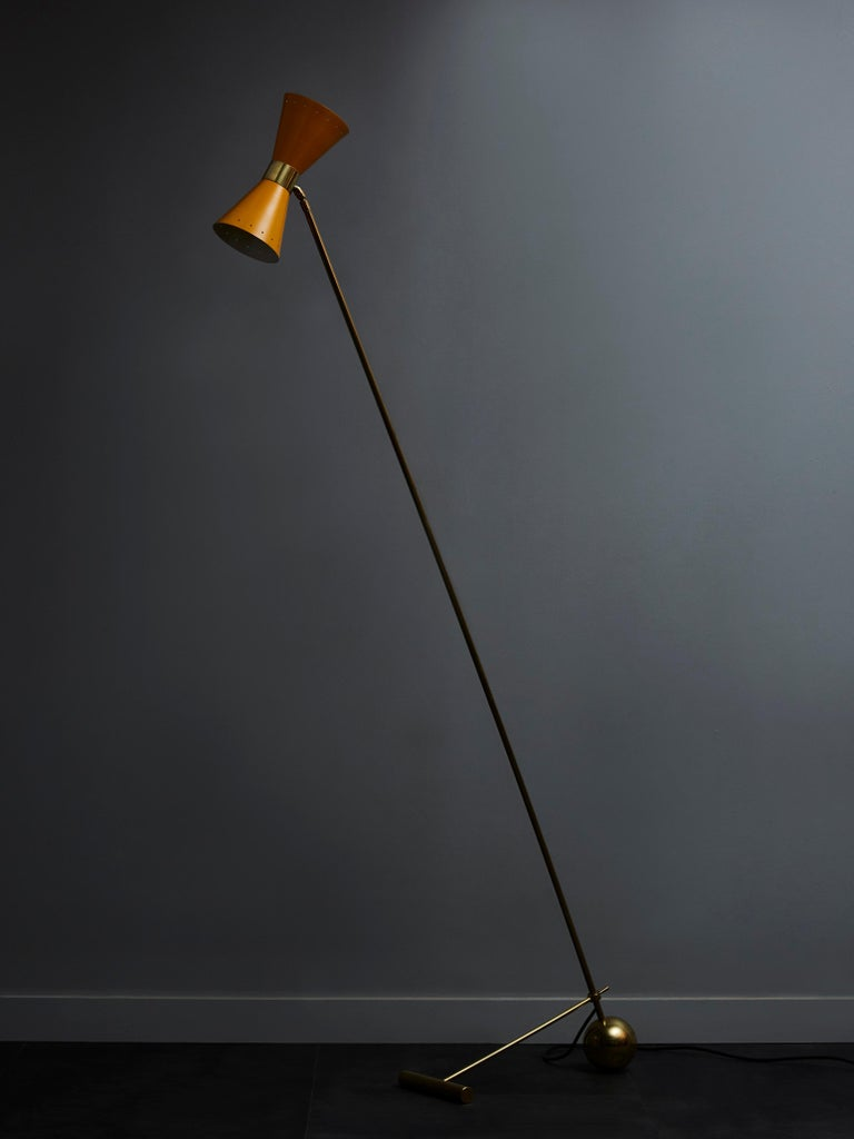 Midcentury style floor lamp made of a long brass arm hold in place by a geometrical foot and holding two yellow cones each hosting a single light.