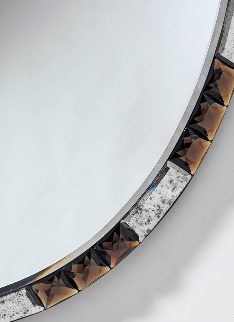 Midcentury style oval mirror with chamfered edge mounted with alternating antique crystal and topaz crystal stones. 