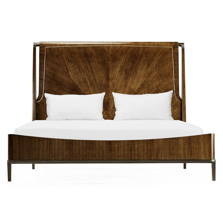 A midcentury style quartered walnut king-size bed with an upholstered headboard and antique brass hardware and feet.  Dimensions: 82 1/4