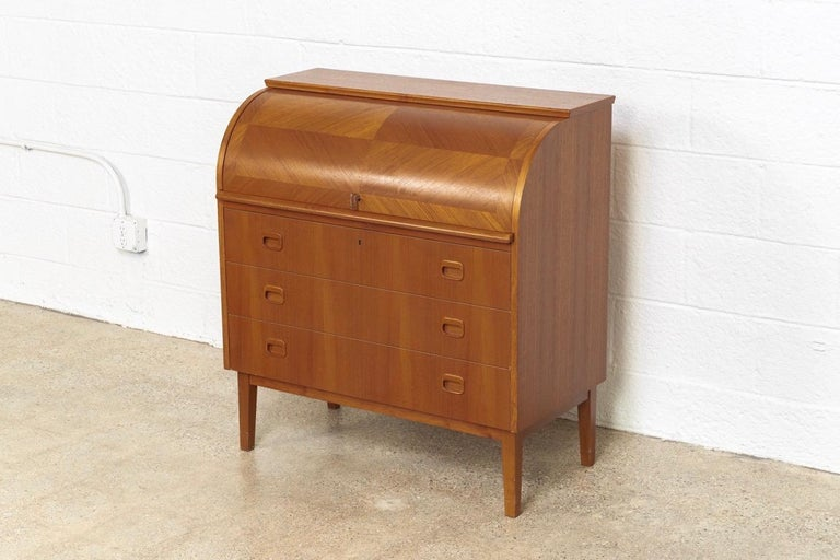 This iconic midcentury Swedish modern Egon Ostergaard teak cylinder rolltop secretary desk cabinet is circa 1970. The Classic Scandinavian modern design has clean Minimalist lines and features a beautiful inlaid opposing-grain pattern rolltop