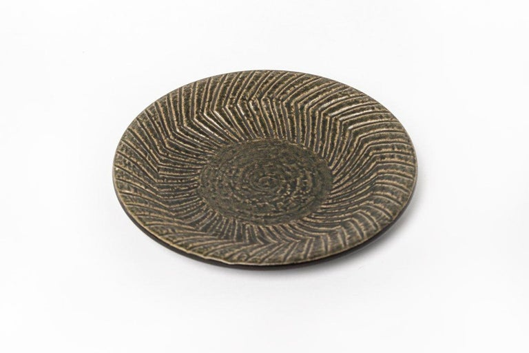 This beautiful vintage Scandinavian modern decorative ceramic plate designed by Mari Simmulson (Swedish, 1911-2000) for Upsala-Ekeby is circa 1960. The modernist design has gentle contours and features a distinctive geometric zig-zag striped