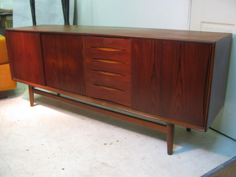 Beautiful vintage teak credenza with a rich and deep patina that has mellowed over the years. Three sliding doors which reveal a large and a small shelf along with five graduated drawers also for storage. Finger slots on all doors and drawers