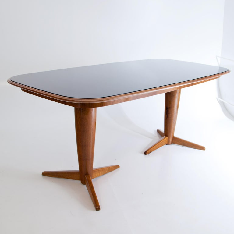 Midcentury table with rectangular table top with rounded corners. The table stands on two legs with three feet each. The table top is colored in black and covered with a glass top.