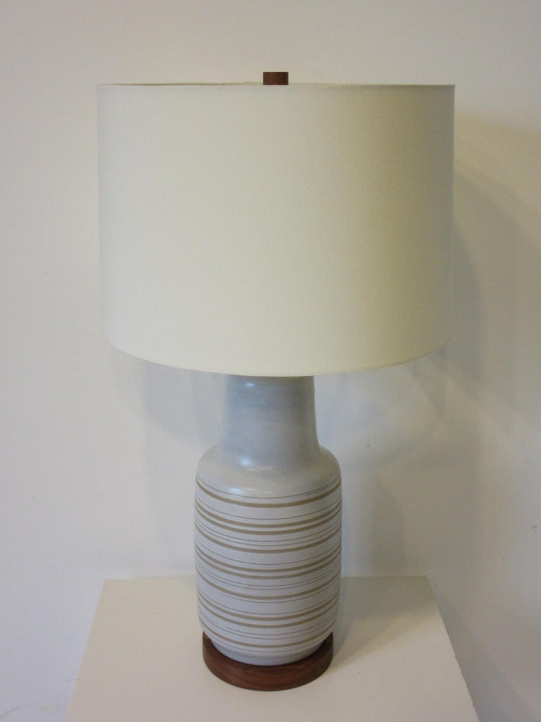 A midcentury pottery table lamp in cream having incised sand tone color stripes with original teak wood base and matching finial. The original shade has been replaced with a high end up to date light cream colored linen shade, the lamp retains the