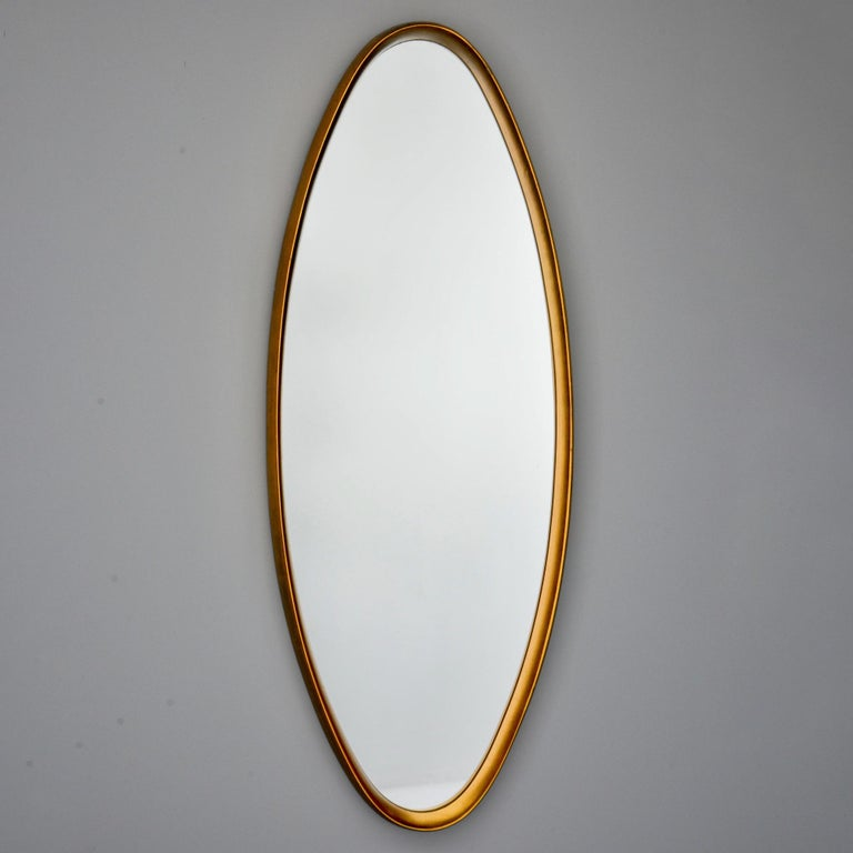 Tall narrow oval mirror with slim, deep set giltwood frame circa 1960s. Unknown maker.