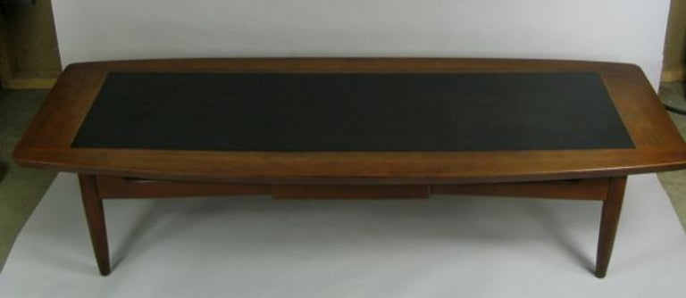 #8-362 Solid walnut  coffee table with black laminate insert and center drawer.