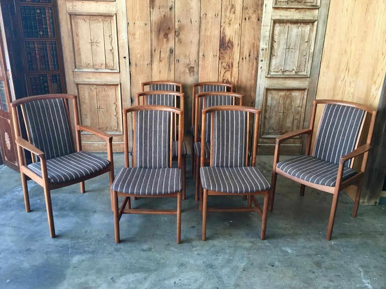 Midcentury set including two armchairs and six side chairs in solid teak with vintage upholstery made in Sweden  The armchairs are 23.5