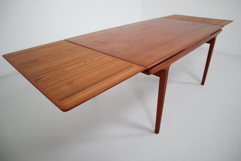 Designed by Niels Møller, this Danish modern extension table is notable for its beautifully tapered lines and the warmth of the teak. Two concealed leaves easily slide out allow ten persons to dine comfortably. Each extension is 50 cm.