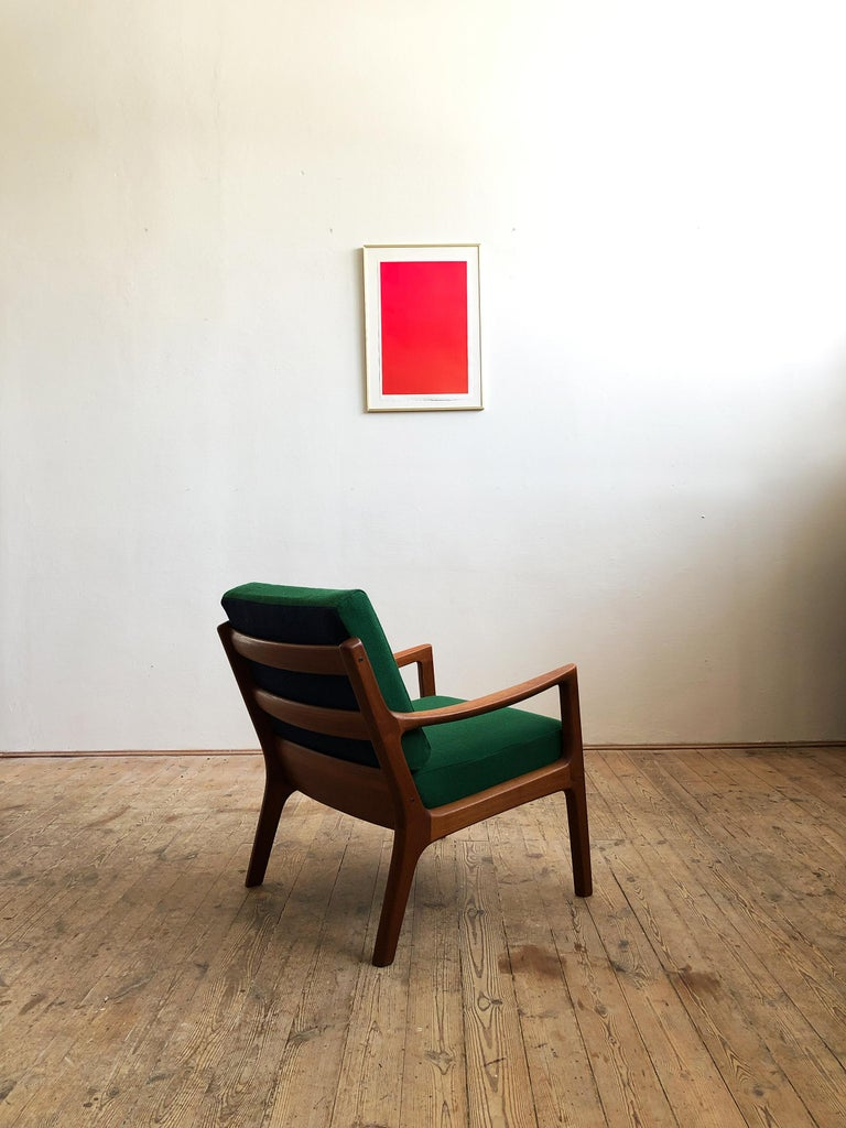This shapely and comfortable easy chair was designed by Ole Wanscher for Poul Jeppesen. This piece comes in a version made of solid teak wood with box spring cushions and new two colored cushions. The woolen fabric called Hallingdal is made by