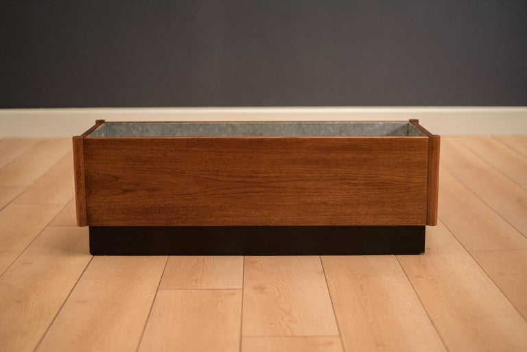 Vintage rectangular planter box in teak with black plinth base. This decorative piece includes a removable galvanized insert tray and is recommended for indoor use.   Interior tray: 33.5