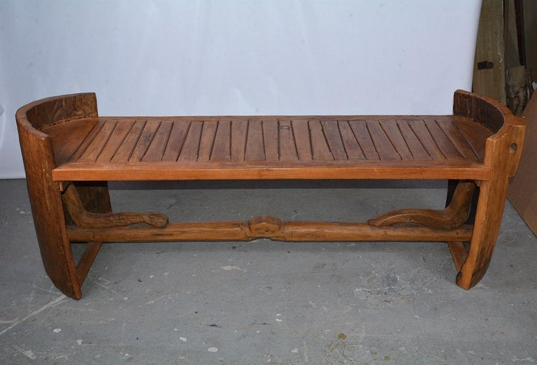 This bench has an amazing form. Each of the two ends constructed from a barrel, believed to be of Asian origin. Bridged together by a hand carved teak seat of geometric design. The lower base is formed of sculptural organic wood, pegged. This piece