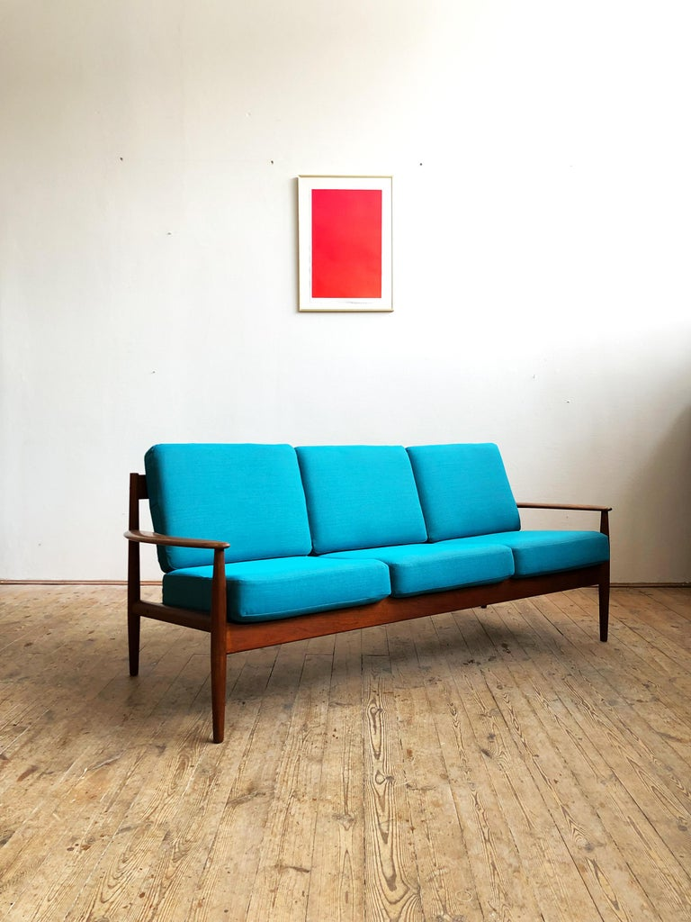Teak sofa produced by France & Son and designed by Grete Jalk. The Sofa shows best Danish quality craftsmanship. It comes with new tight spring cushions with a new upholstery from Danish premium Manufacturer Kvadrat (Steelcut Trio).