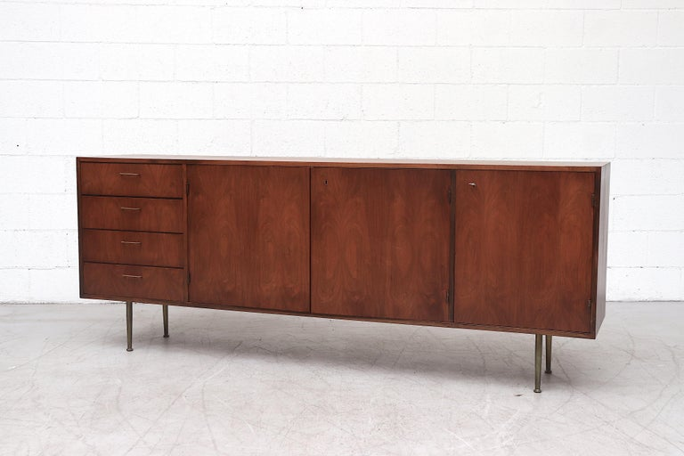 Beautiful mid-century teak credenza lightly refinished with amazing wood grain. Four side stacked drawers, all with delicate brass handles. Top drawer is felt lined with flatware storage. Double storage cabinets and bottle /glass storage in the